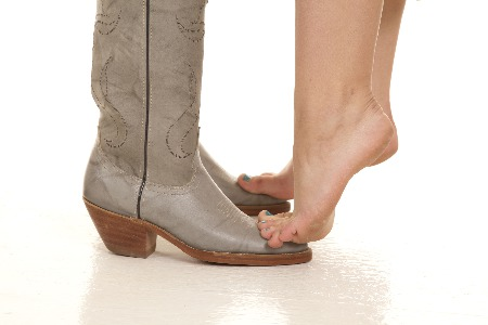 Bare female feet on tip-toe standing on cowboy boots